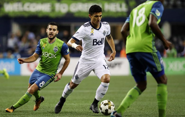 Seattle's Victor Rodriguez (8) guards Vancouver's Fredy Montero (12) during the first half of the Seattle Sounders FC versus Vancouver Whitecaps FC came at CenturyLink Field in Seattle Wash. Wednesday, Sept. 27, 2017. (Erika Schultz / The Seattle Times)