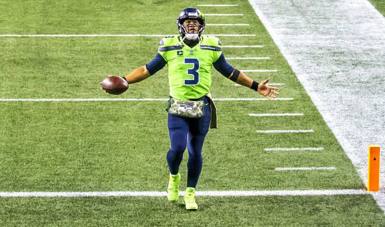 Seahawks quarterback Russell Wilson looks up to the sky as he comes onto the field and steps into the end zone before the start of a game vs. Cardinals on Thursday, Nov. 19, 2020. (Bettina Hansen / The Seattle Times)