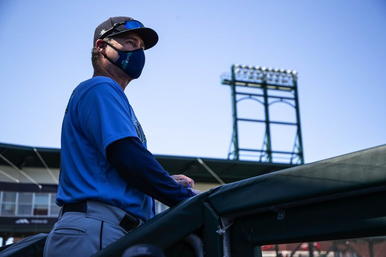 Mariners manager Scott Servais stands at the top of the Mariners dugout during Wednesday's game with the Chicago Cubs.  (Dean Rutz / The Seattle Times)