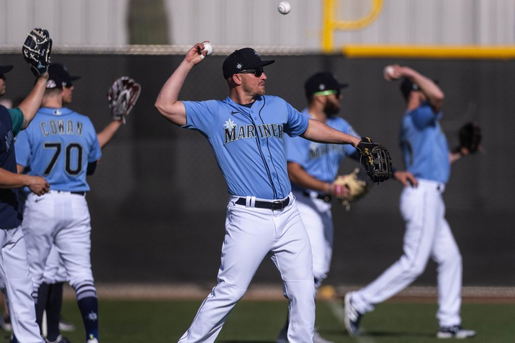 Kyle Seager and Mariners infielders warm up for practice late last month at Peoria Sports Complex in Arizona. (Dean Rutz / The Seattle Times)