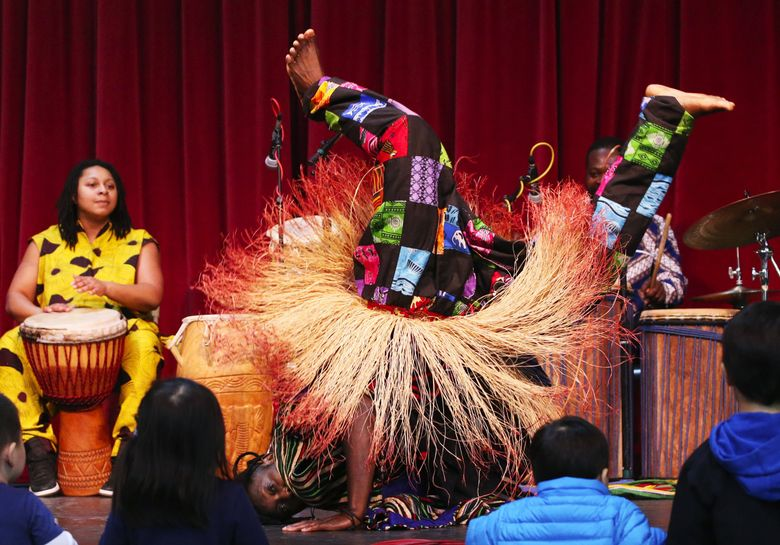 """Children hug the stage as Kokou Gbakenou, with Gansango Music and Dance Company, performs a traditional harvest dance of Togo called """"Idjombi"""" as part of Seattle's French Fest in 2019 at Seattle Center. French is the official language in Togo, where Seattleite Gbakenou is originally from. This year's event will be virtual. (Ken Lambert / The Seattle Times)"""