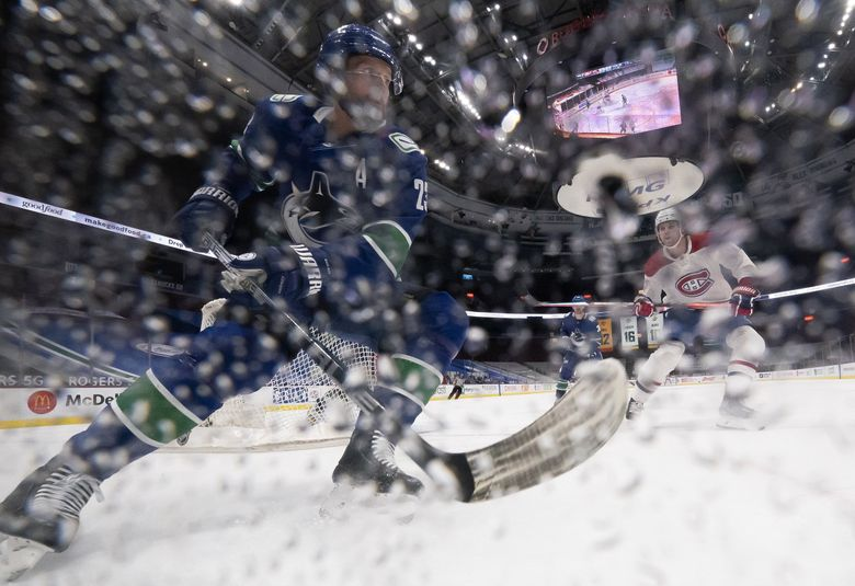 Vancouver Canucks defenseman Alexander Edler (23) stops along the boards as Montreal Canadiens right wing Josh Anderson (17) follows during the second period of an NHL hockey game Wednesday, March 10, 2021, in Vancouver, British Columbia.  (JONATHAN HAYWARD / The Associated Press)