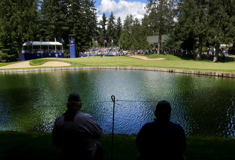 Norman Abbott, left, and his wife, Janet Nelson, watch competitors from across the lake on the 9th hole on day two of the KPMG Women's PGA Championship on Friday, June 10, 2016, at Sahalee Country Club in Sammamish. (Johnny Andrews / The Seattle Times)