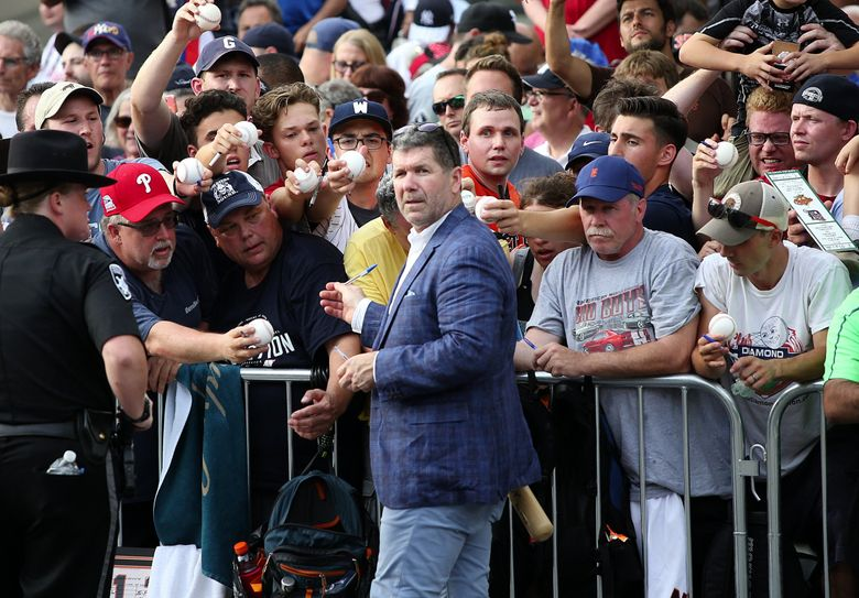 Edgar Martinez pauses a moment from signing autographs at the 2019 National Baseball Hall of Fame inductee parade route in Cooperstown, NY. (Ken Lambert / The Seattle Times)