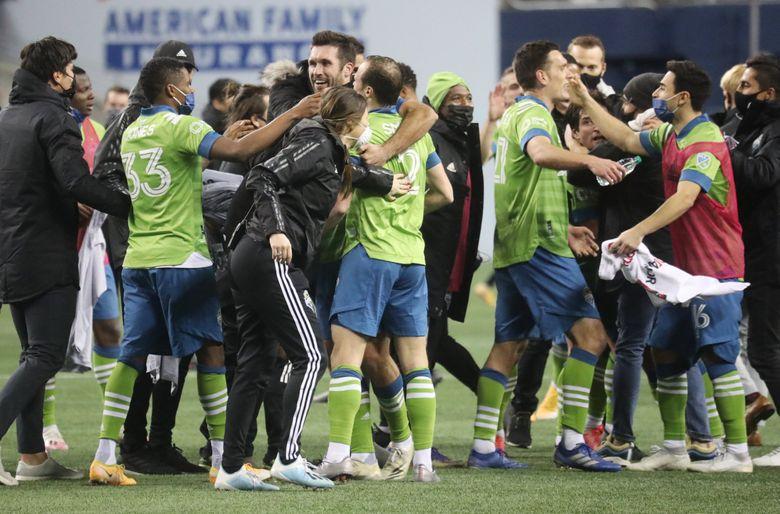The Seattle Sounders celebrate winning the MLS Western Conference Finals match against Minnesota, Monday, Dec. 7, 2020 at Lumen Field in Seattle.  (Ken Lambert / The Seattle Times)