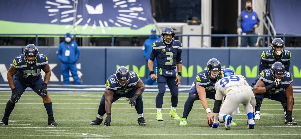 Offensive linemen from left, Cedric Ogbuehi, Damien Lewis, Ethan Pocic and Jordan Simmons line up in front of quarterback Russell Wilson and running back Carlos Hyde as the Seattle Seahawks take on the Los Angeles Rams at Lumen Field in Seattle, on Sunday Dec. 27, 2020.  (Bettina Hansen / The Seattle Times)