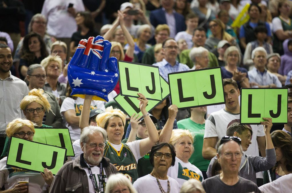 """Fans wear blond wigs and hold """"LJ"""" signs after the July 15, 2016, game between the Seattle Storm and Washington Mystics at KeyArena. Former Storm player Lauren Jackson, who was drafted in 2001 and spent her entire WNBA career in Seattle before injuries forced her to retire, was honored this night with the retirement of her jersey number, 15. Jackson helped the Storm win WNBA championships in 2004 and 2010, is a 7-time WNBA All-Star and three-time league MVP, among other accolades. (Lindsey Wasson / The Seattle Times)"""