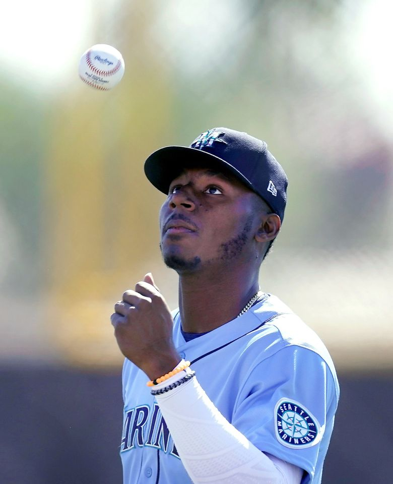 Kyle Lewis catches a ball during spring training baseball practice Thursday, Feb. 25, 2021, in Peoria, Ariz. (Charlie Riedel / The Associated Press)