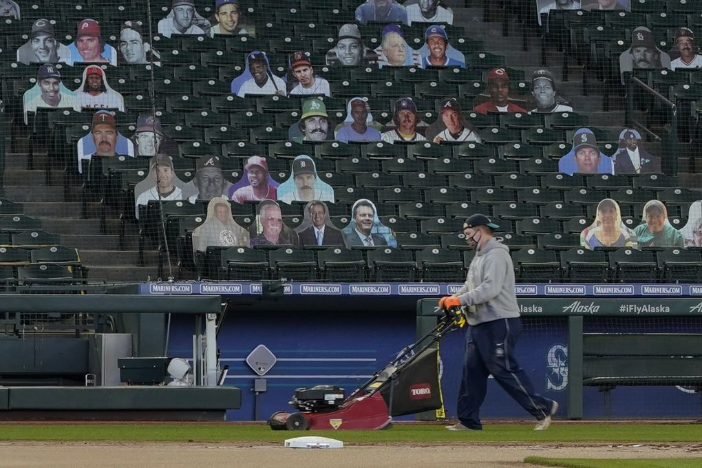 """A grounds crew worker mows grass near the first-base foul line at T-Mobile Park, the home of the Seattle Mariners baseball team, Monday, March 22, 2021, in Seattle, as photos in the stands demonstrate how fans attending reduced-capacity games will be separated into """"seating pods"""" to avoid the spread of COVID-19. The Mariners will host the San Francisco Giants on April 1 in the Mariners' home-opener. (Ted S. Warren / The Associated Press)"""