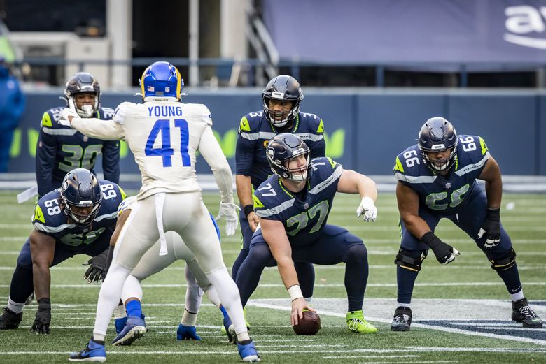 Seahawks quarterback Russell Wilson lines up behind center Ethan Pocic and offensive linemen Damien Lewis, left, and Jordan Simmons, right, as the Seattle Seahawks take on the Los Angeles Rams at Lumen Field in Seattle, Sunday December 27, 2020. (Bettina Hansen / The Seattle Times)