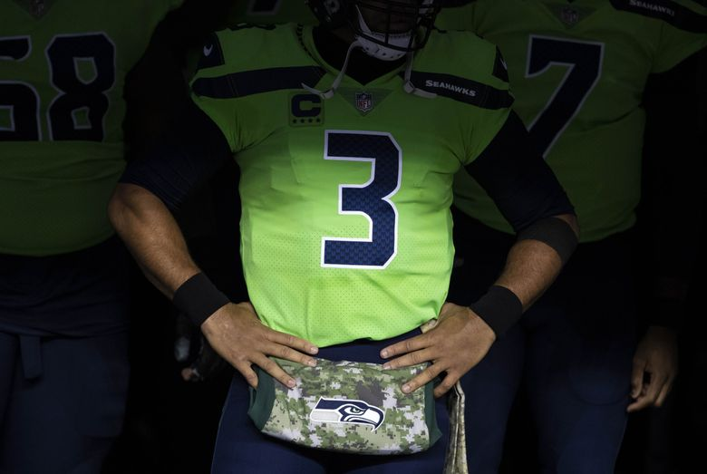 Russell Wilson prepares to take the field against the Arizona Cardinals for a Thursday night game in Seattle last season. (Dean Rutz / The Seattle Times)