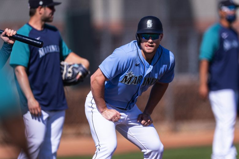 Jarred Kelenic watches the coaches instruction from third base during base-running drills last month. (Dean Rutz / The Seattle Times)
