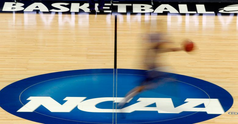 FILE – In this March 14, 2012, file photo, a player runs across the NCAA logo during practice in Pittsburgh before an NCAA tournament college basketball game. NCAA basketball administrators apologized to the women's basketball players and coaches after inequities between the men's and women's tournament went viral on social media. Administrators vowed to do better. NCAA Senior Vice President of Basketball Dan Gavitt spoke on a zoom call Friday, March 19, 2021, a day after photos showed the difference between the weight rooms at the two tournaments. (AP Photo/Keith Srakocic, File)