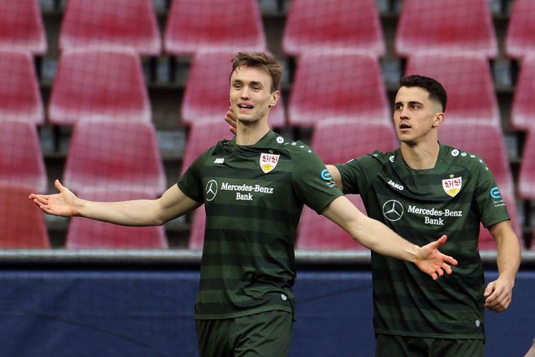 Stuttgart's Sasa Kalajdzic, left, celebrates Marc Oliver Kempf after he scores the opening goal during the German Bundesliga soccer match between 1. FC Koeln and VfB Stuttgart in Cologne, Germany, Saturday, Feb. 20, 2021.( Rolf Vennenbernd/dpa via AP)