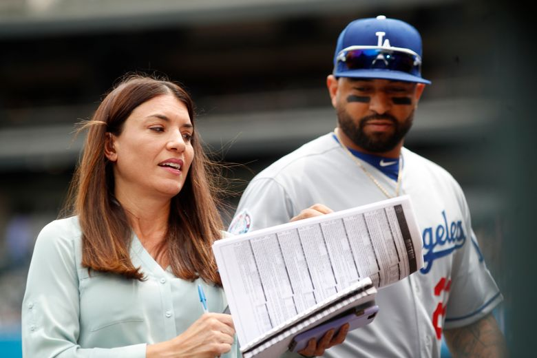 """FILE – Los Angeles Dodgers announcer Alanna Rizzo, left, delivers a report before the first inning of a baseball game against the Colorado Rockies in Denver, with Dodgers left fielder Matt Kemp looking on in Denver, in this Sunday, June 3, 2018, file photo. Rizzo is returning to MLB Network, and will be a regular contributor on Christopher Russo's """"High Heat"""" show. (AP Photo/David Zalubowski, File)"""