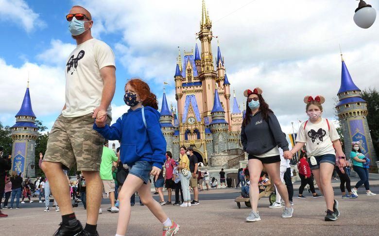 FILE – In this Dec. 21, 2020, file photo, a family walks past Cinderella Castle in the Magic Kingdom, at Walt Disney World in Lake Buena Vista, Fla. (Joe Burbank/Orlando Sentinel via AP, File)