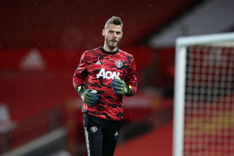 """FILE – In this Saturday Feb. 6, 2021 file photo, Manchester United's goalkeeper David de Gea warms up before their English Premier League soccer match against Everton at the Old Trafford stadium in Manchester, England. Manchester United manager Ole Gunnar Solskjaer says goalkeeper David De Gea will have """"the time he needs"""" before returning to the team following a trip to Spain for the birth of his child. De Gea is unavailable for the Manchester derby on Sunday, March 7 and missed Wednesday's 0-0 draw with Crystal Palace after he and his girlfriend traveled to Spain for the birth. (Alex Pantling/Pool via AP, file)"""