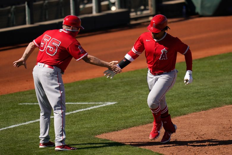 Los Angeles Angels' Jon Jay, right, celebrates his home run with third base coach Brian Butterfield (55) during the sixth inning of a spring training baseball game against the Cleveland Indians, Wednesday, March 10, 2021, in Goodyear, Ariz. (AP Photo/Ross D. Franklin)