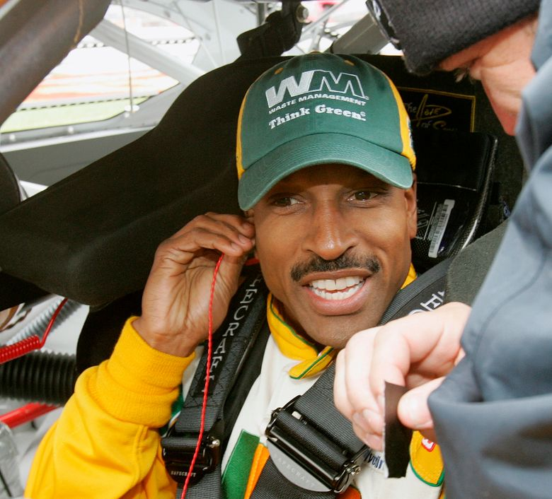 FILE – NASCAR driver Bill Lester gets ready for a rain delayed start of the NASCAR Golden Corral 500 auto race at Atlanta Motor Speedway, in Hampton, Ga., in this Monday, March 20, 2006, file photo. Bill Lester, one of the first Black drivers to compete in NASCAR's Truck Series, will return to competition 14 years after his last start.  Lester will drive for David Gilliland Racing on Saturday, March 20, 2021, in the Truck Series race at Atlanta Motor Speedway. It will be the first NASCAR start for the 60-year-old since 2007. (AP Photo/Ric Feld, File)