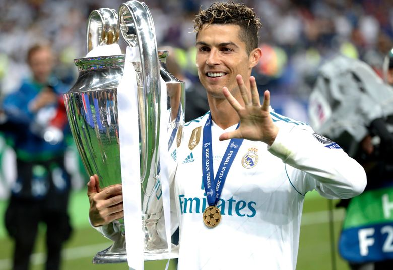 FILE – In this Saturday, May 26, 2018 file photo Real Madrid's Cristiano Ronaldo celebrates with the trophy after winning the Champions League Final soccer match between Real Madrid and Liverpool at the Olimpiyskiy Stadium in Kiev, Ukraine. Neither Lionel Messi nor Cristiano Ronaldo will be in the Champions League quarterfinals for the first time since 2005. The two greatest players of the current generation were both eliminated from the competition this week. Messi scored a goal but missed a penalty as Barcelona was eliminated by Paris Saint-Germain. Ronaldo and his Juventus teammates were ousted by Porto the night before. Ronaldo has won five Champions League titles in his career. Messi has won four. (AP Photo/Pavel Golovkin, File)
