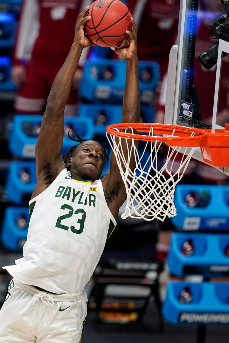 FILE – Baylor forward Jonathan Tchamwa Tchatchoua (23) goes up for a dunk against Wisconsin in the first half of a second-round game in the NCAA men's college basketball tournament at Hinkle Fieldhouse in Indianapolis, in this Sunday, March 21, 2021, file photo. All-American junior Jared Butler and his backcourt mates Davion Mitchell and MaCio Teague pretty much get all of the attention for the top-seeded Bears (26-2), who play a former Southwest Conference rival in the first national semifinal game Saturday. But those guards know they wouldn't be where they are now without the often interchangeable 245-pound post players _ the 6-foot-10 Thamba and and 6-8 Tchamwa Tchatchoua. (AP Photo/Michael Conroy, File)