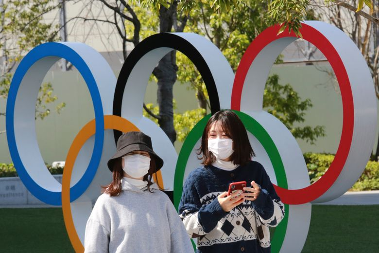 FILE – In this March 17, 2021, file photo, people walk past the Olympic rings in Tokyo. The Tokyo Olympics open in under four months, and the torch relay has begun to crisscross Japan with 10,000 runners. Organizers say they are mitigating the risks, but many medial expert aren't convinced.(AP Photo/Koji Sasahara)