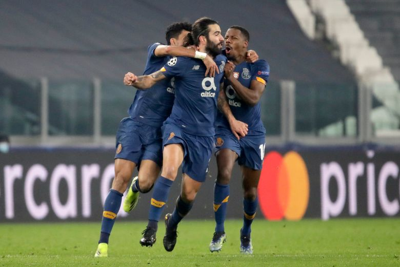 Porto's Sergio Oliveira, center, celebrates after scoring his side's second goal during the Champions League, round of 16, second leg, soccer match between Juventus and Porto in Turin, Italy, Tuesday, March 9, 2021. (AP Photo/Luca Bruno)