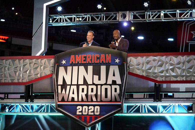 """This image released by NBC shows hosts Matt Iseman, left, and Akbar Gbajabiamila on the set of """"American Ninja Warrior."""" Young TV viewers may be getting the message that fame is less important than values like achievement and a sense of community. That's according to a new study from the University of California, Los Angeles. In examining the TV shows most popular with children ages 8 to 12, knowns as """"tweens,"""" researchers found that the emphasis on fame diminished in 2017. (Elizabeth Morris/NBC via AP)"""