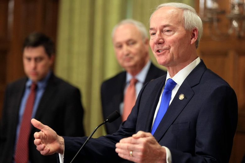 FILE – In this March 23, 2020 file photo, Arkansas Gov. Asa Hutchinson, right, speaks during a news conference in Little Rock, Ark. Gov. Hutchinson on Thursday, March 25, 2021 signed a law banning transgender women and girls from competing in school sports teams consistent with their gender identity. (Staton Breidenthal/The Arkansas Democrat-Gazette via AP)