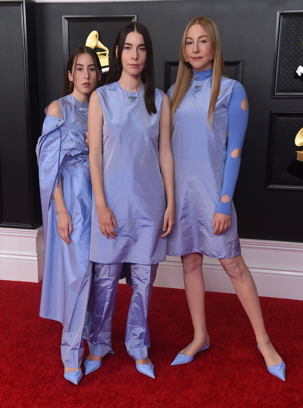 Alana Haim, from left, Danielle Haim and Este Haim, of HAIM, arrive at the 63rd annual Grammy Awards at the Los Angeles Convention Center on Sunday, March 14, 2021. (Jordan Strauss / Invision / The Associated Press)