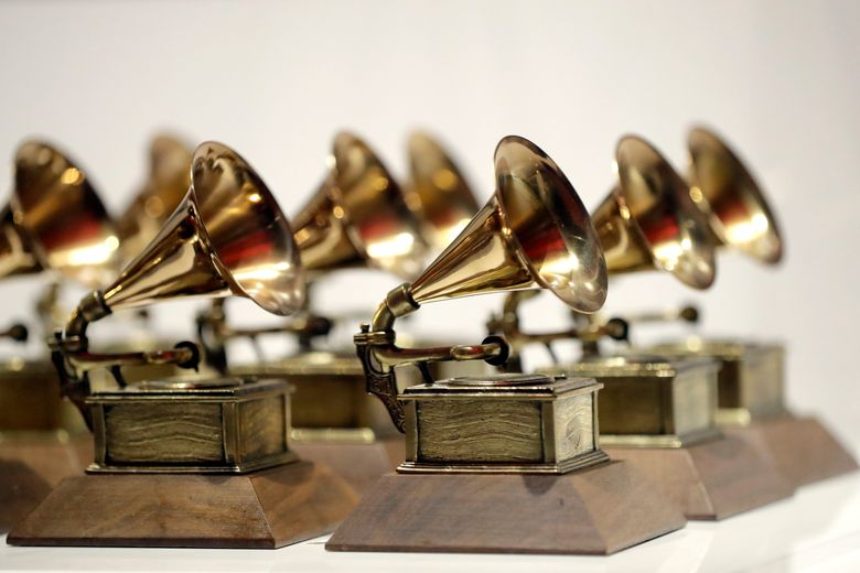 """FILE – In this Oct. 10, 2017, file photo, various Grammy Awards are displayed at the Grammy Museum Experience at Prudential Center in Newark, N.J. The Recording Academy is partnering with Berklee College of Music and Arizona State University to complete a study focused on women's representation in the music industry.. The academy, which puts on the annual Grammy Awards, said the lack of female creators in music is """"one of the most urgent issues in the industry today."""" (AP Photo/Julio Cortez, File)"""