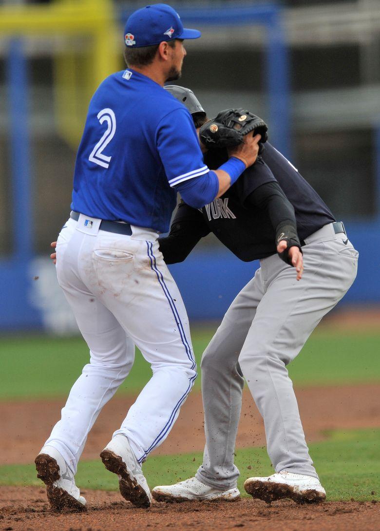 Toronto Blue Jays third baseman Joe Panik (2) tags out New York Yankees' Tyler Wade on a rundown during the second inning of a spring training baseball game Sunday, March 21, 2021, at TD Ballpark in Dunedin, Fla.   (Steve Nesius/The Canadian Press via AP)