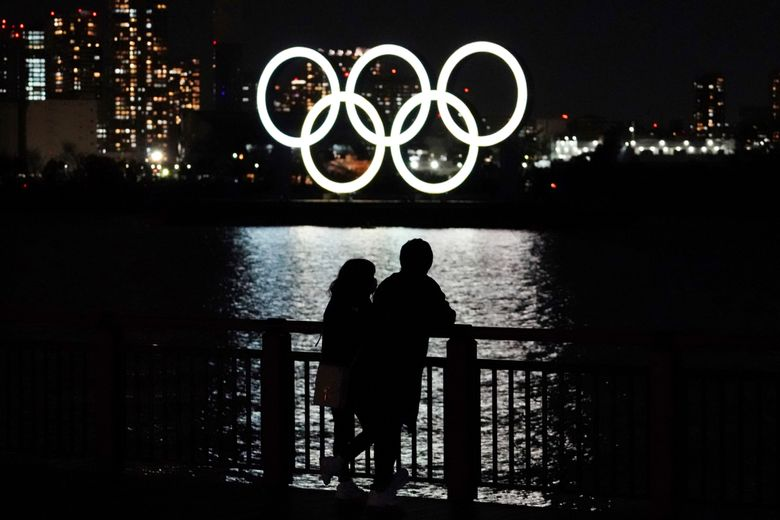A man and a woman stand with the backdrop of the Olympic rings floating in the water in the Odaiba section in Tokyo, Wednesday, March 3, 2021. (AP Photo/Eugene Hoshiko)