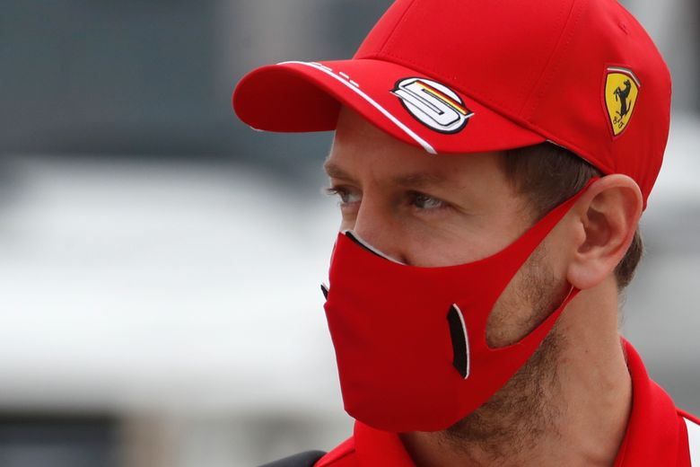 FILE – In this Friday, Nov. 27, 2020 file photo, Ferrari driver Sebastian Vettel of Germany arrives at the paddock ahead of the first free practice at the Formula One Bahrain International Circuit in Sakhir, Bahrain. The new season starts Sunday March 28, 2021 with the Bahrain Grand Prix and ends in December 2021 at Abu Dhabi. (Hamad Mohammed, Pool via AP, File)