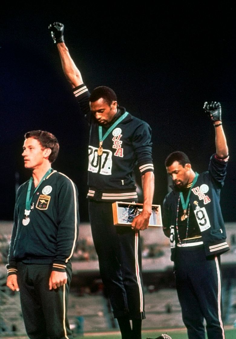 """FILE – In this Oct. 16, 1968, file photo, U.S. athletes Tommie Smith, center, and John Carlos extend gloved hands skyward in racial protest during the playing of national anthem after Smith received the gold and Carlos the bronze for the 200 meter run at the Summer Olympic Games in Mexico City. Australian silver medalist Peter Norman is at left. The U.S. Olympic and Paralympic Committee will allow raised fists and kneeling during the national anthem at upcoming Olympic trials. The USOPC released a nine-page document to offer guidance about the sort of """"racial and social demonstrations"""" that will and won't be allowed by the hundreds of athletes who will compete for spots on the U.S. team in various sports. (AP Photo/File)"""