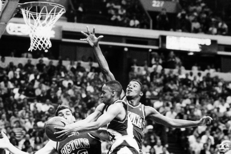 FILE – In this March 21, 1989, file photo, Atlanta Hawks Spud Webb is blocked by Detroit Pistons Bill Laimbeer and Isiah Thomas as he drives to the basket during an NBA basketball game in Atlanta. Webb remembers getting on the bus after winning the NBA slam dunk contest 35 years ago and getting a quick piece of advice from his Atlanta teammate at the time, Doc Rivers. The message: Your life just changed forever. That's what happens when a 5-foot-7 guy captures imaginations by winning the dunk contest, which was just in its third year then. (AP Photo/JHJR, File)