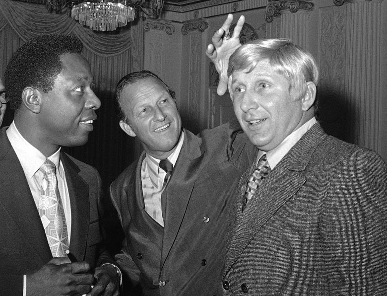 FILE In this Jan. 25, 1971, file photo, Stan Musial, center, vice president of the St. Louis Cardinals, jokes around as he reaches to feel a blond wig worn by Joe Cunningham, right, manager of the Cardinals, as Atlanta Braves' Hank Aaron, left, watches in St. Petersburg, Fla. Cunningham, who got off to a smashing start with the Cardinals and later became a minor league manager, major league coach, key figure in their front office and team ambassador, has died. He was 89. (AP Photo/Fred Waters, File)