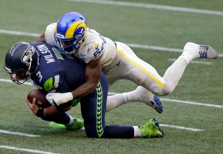 FILE – In this Dec. 27, 2020, file photo, Seattle Seahawks quarterback Russell Wilson (3) is sacked by Los Angeles Rams outside linebacker Leonard Floyd (54) during the first half of an NFL football game in Seattle. Floyd is overjoyed to be back with the Rams after producing a career-high 10 ½ sacks for Los Angeles last season. He believes the Rams are a Super Bowl contender with a defense that was the best in the NFL last season. (AP Photo/Scott Eklund, File)