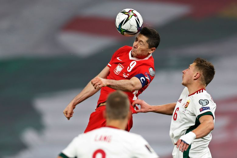 Poland's Robert Lewandowski, centre, jumps to head the ball during the World Cup 2022 group I qualifying soccer match between Hungary and Poland at the Puskas Arena in Budapest, Hungry Thursday March 25, 2021. (AP Photo/Laszlo Balogh)
