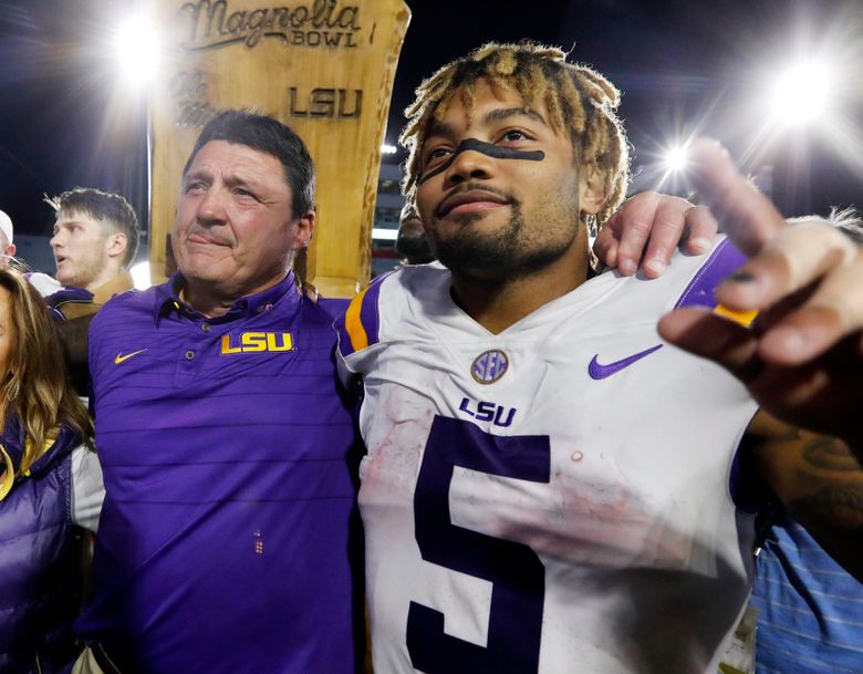 FILE – In this Oct. 21, 2017, file photo, LSU head coach Ed Orgeron, left, celebrates with running back Derrius Guice (5) following a win over Mississippi in an NCAA college football game in Oxford, Miss. A 74-year-old woman told state lawmakers she spoke directly to Orgeron about sexual harassment she endured in 2017 from one of his star players. But the woman, a grandmother, said Orgeron did nothing to reprimand then-LSU running back Guice when the player allegedly harassed her while she working at her Superdome security job in 2017. (AP Photo/Rogelio V. Solis, File)