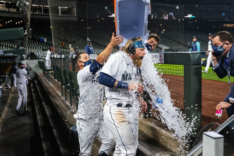 Ty France, left, and Dylan Moore get Jake Fraley with the ice bath after Fraley walked to force across the winning run in the 10th. The San Francisco Giants played the Seattle Mariners in the season opener for both teams Thursday, April 1, 2021 at T-Mobile Park in Seattle, WA.  (Dean Rutz / The Seattle Times)