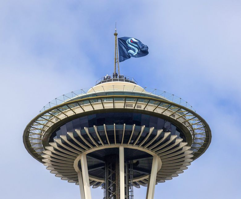 The NHL Seattle Kraken logo flies from the Space Needle shortly after the name was announced, Thursday, July 23, 2020 in Seattle.  (Ken Lambert / The Seattle Times)
