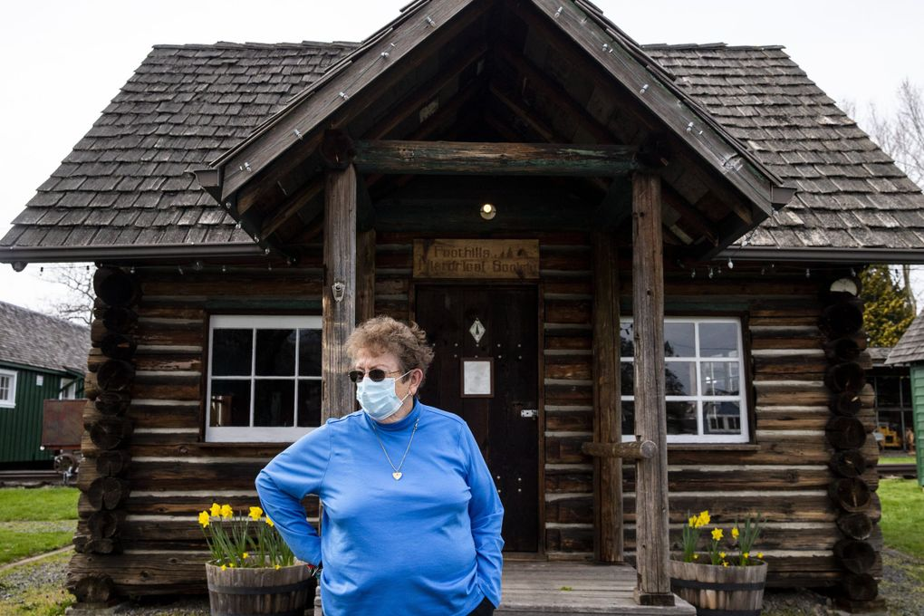 Martha Olsen, curator for the Foothills Historical Museum, in front of a log cabin that was built as Washington State Forestry Department guard station. It was located at Swede Point and moved when the White River eroded the riverbank out from under it. (Amanda Snyder / The Seattle Times)