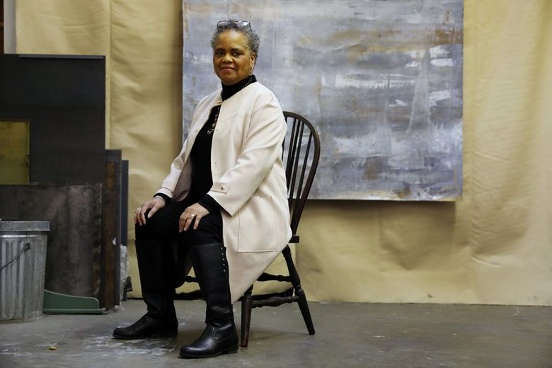 """Valerie Curtis-Newton, founding artistic director of The Hansberry Project, in 2019. In the background is part of an acrylic painting by Curtis-Newton's wife, Kim Powell, called """"Typical Winter Day."""" (Ken Lambert / The Seattle Times)"""