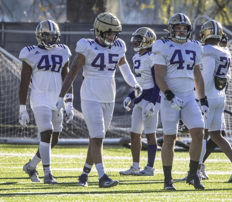 Washington linebackers (from left) Edefuan Ulofoshio, Bralen Trice and Jackson Sirmon walk downfield during Monday's spring football practice on campus. (Steve Ringman / The Seattle Times)