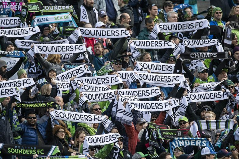 Sounders fans with their scarves up on March 1, 2020 at CenturyLink Field in Seattle, WA. (Dean Rutz / The Seattle Times)