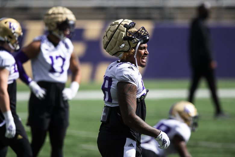 Huskies outside linebacker Zion Tupuola-Fetui chats with teammates as the Huskies participate in their spring practice at Husky Stadium Saturday April 10, 2021 in Seattle. (Bettina Hansen / The Seattle Times)