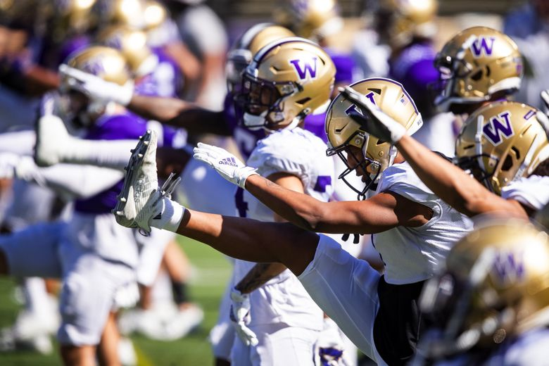 Players warm up as the University of Washington Huskies participate in spring practice at Husky Stadium Saturday April 17, 2021 in Seattle. (Bettina Hansen / The Seattle Times)