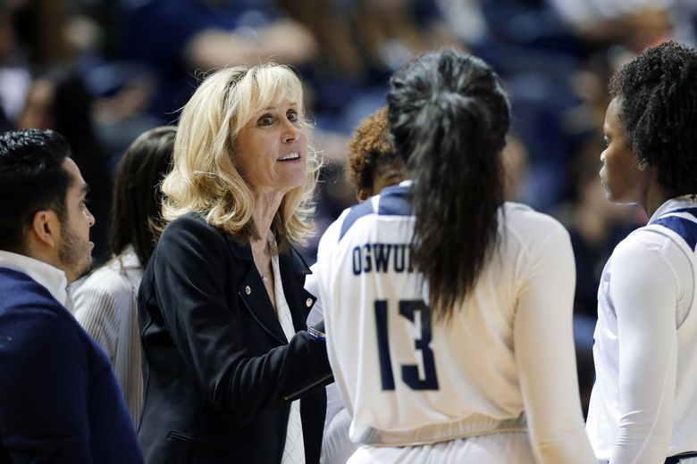 New Washington women's basketball coach Tina Langley talks with her players at Rice during a timeout. (Michael Wyke / The Associated Press)