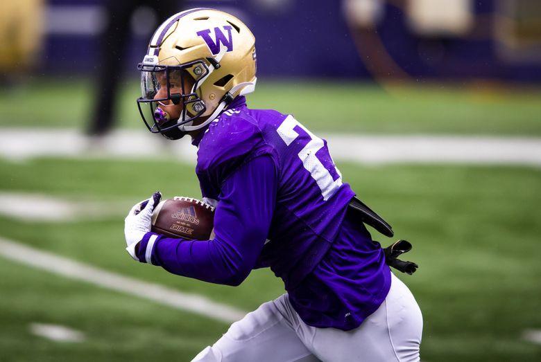 Huskies tailback Cameron Davis runs the ball during spring practice with the University of Washington football team at Husky Stadium Saturday April 24, 2021.  (Bettina Hansen / The Seattle Times)